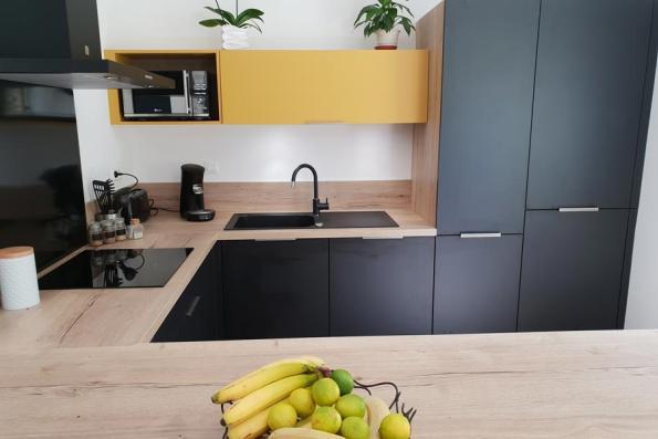 Touche de couleur jaune dans la cuisine noire et bois