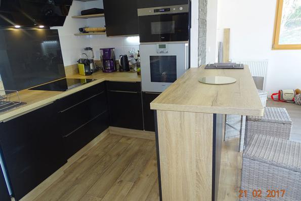 Cuisine noire et bois ouverte sur le salon