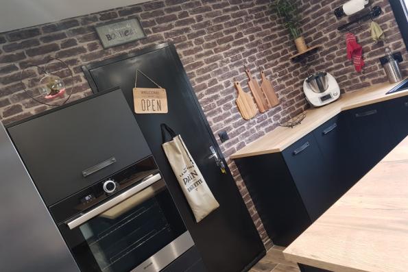 Cuisine noire et bois avec mur en briques vintage