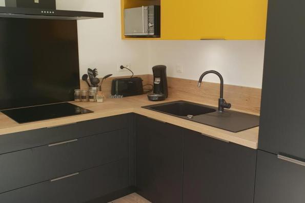 Cuisine équipée jaune et noire avec électroménager intégré