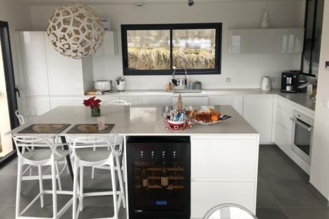 Cuisine blanche avec plan quartz et cave à vin, une cuisine réalisée par SoCoo'c Annecy